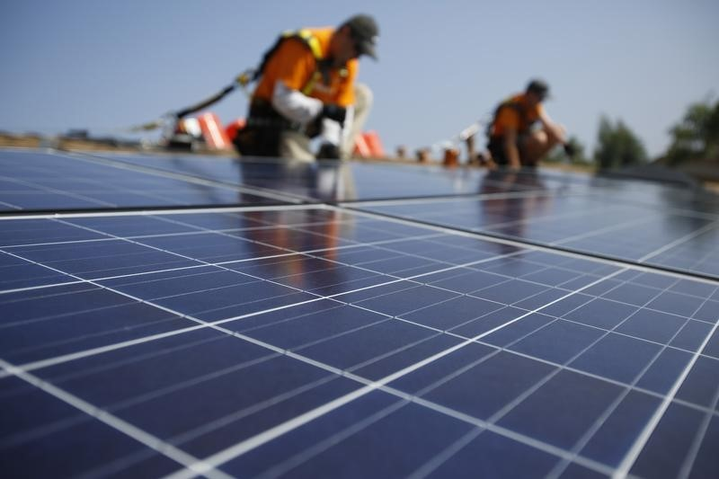 Vivint Solar technicians install solar panels on the roof of a house in Mission Viejo, California October 25, 2013.  REUTERS/Mario Anzuoni